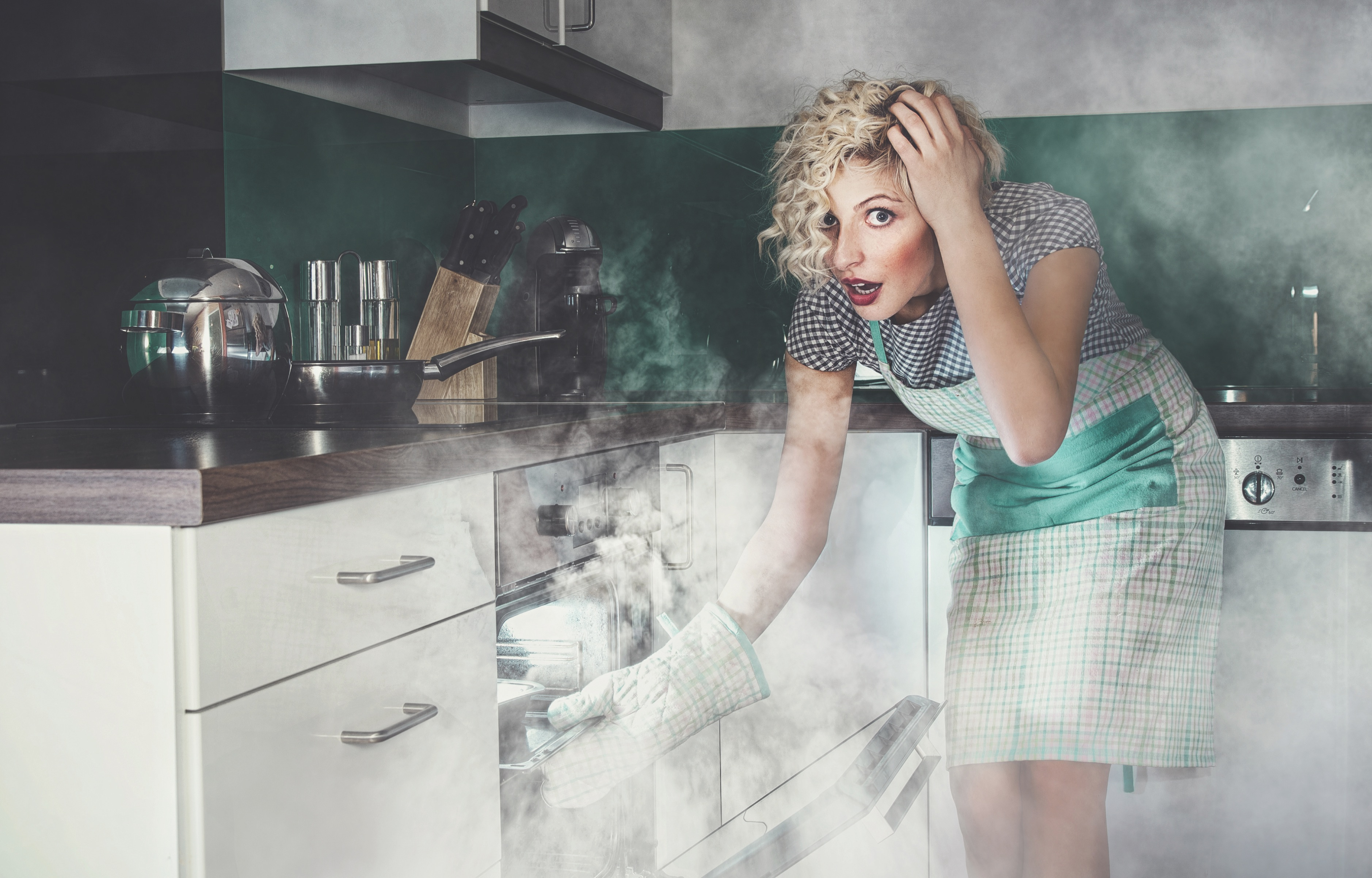 Astonished woman cook or housewife frying lunch in a oven. Smoke, vapor around in the kitchen or home. Creative photo