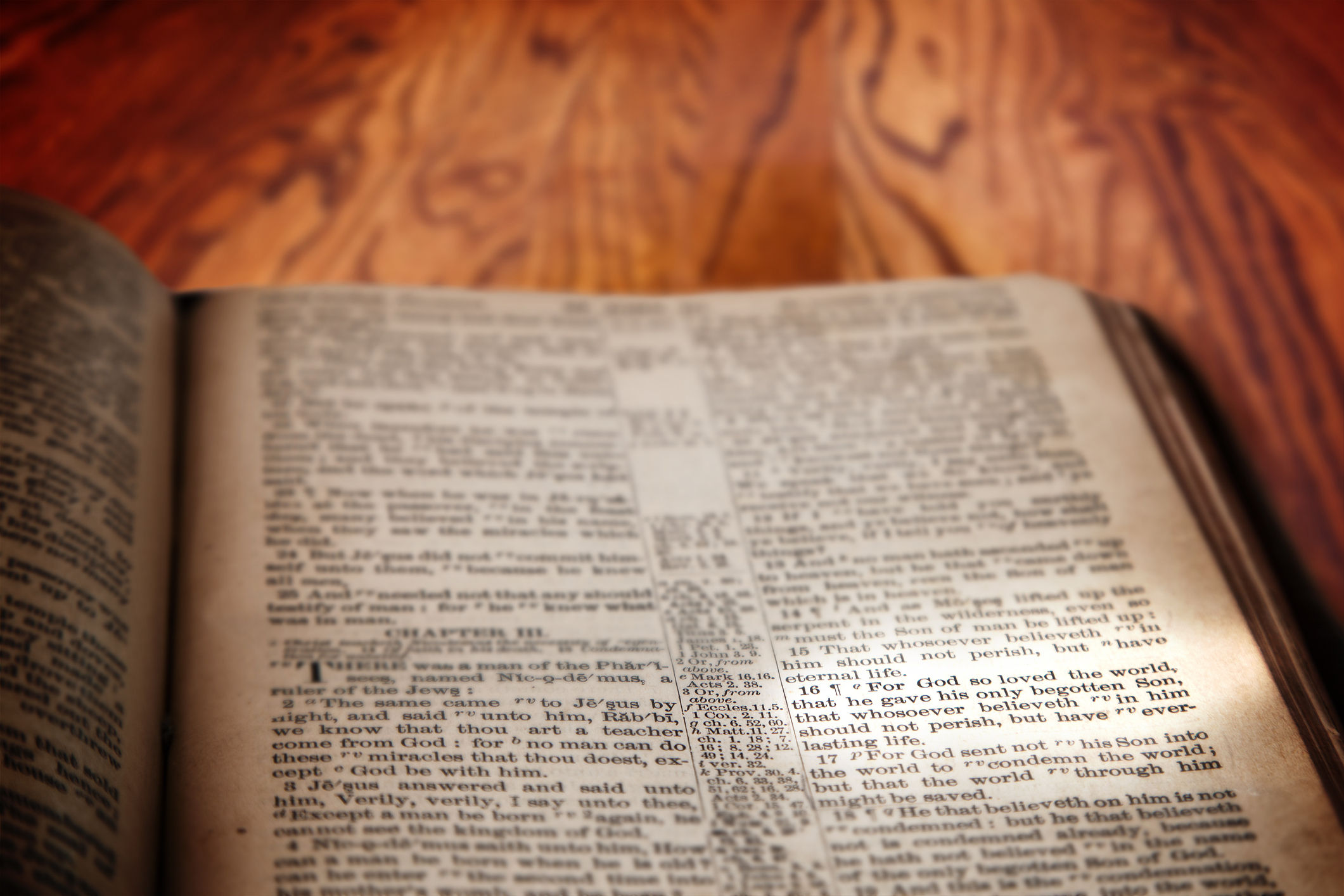 Closeup of an old Holy Bible opened to the famous verse of John 3:16 and highlighted by a beam of light. Book rests on a rustic wooden table with deliberate focus on the verse with shallow depth of field on background. This translation is King James, which is public domain.