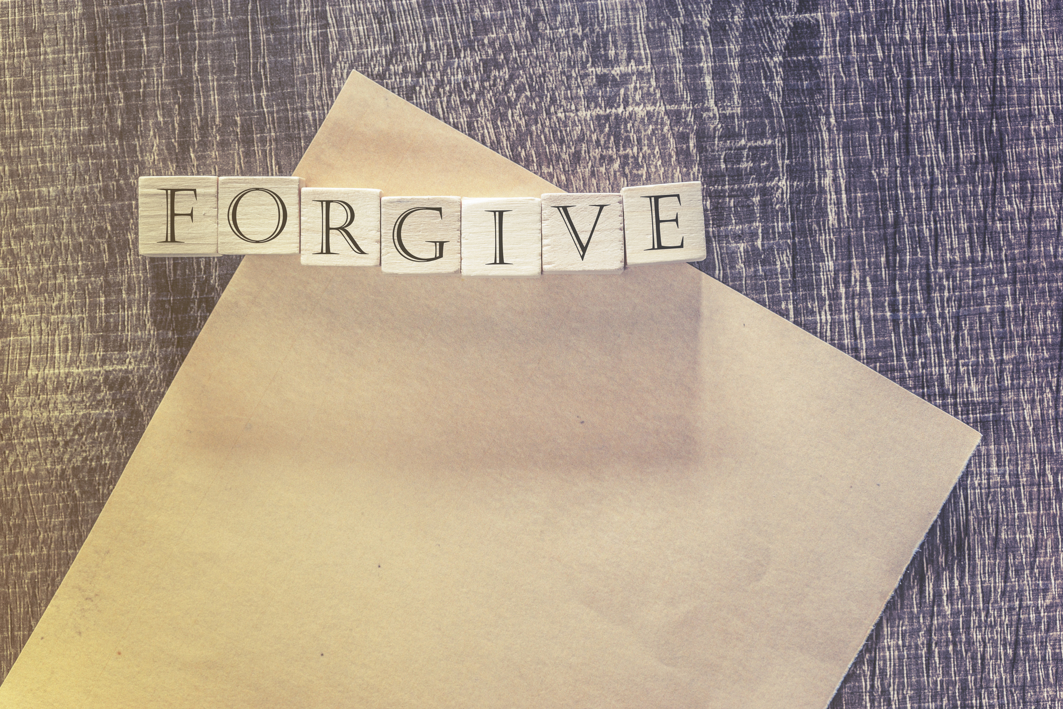 Forgiveness concept. Wooden blocks forming Forgive word on top of a blank paper. Cross processed image for vintage feeling