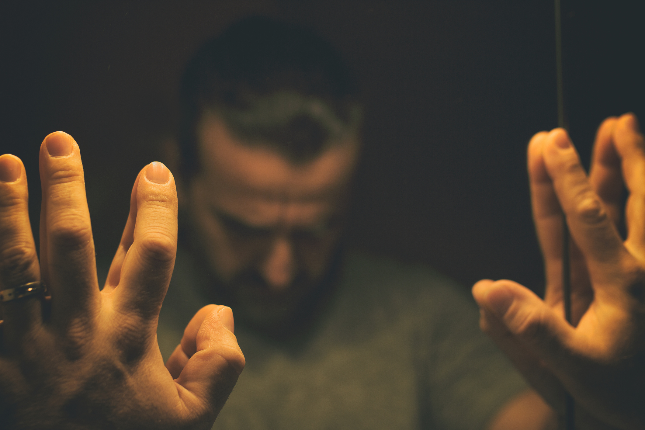 Man in despair with raised hands and bowed headd, in a low light room looking in front of mirror